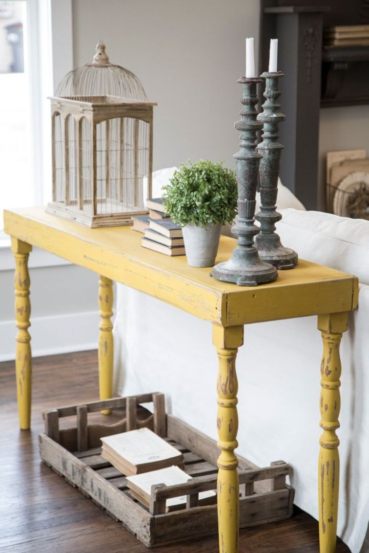 A vintage style yellow table displays decor and adds a pop of color to the living room, as seen on HGTV's Fixer Upper. Detail